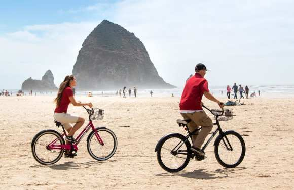 Two people riding bike on a Oregon Beach.