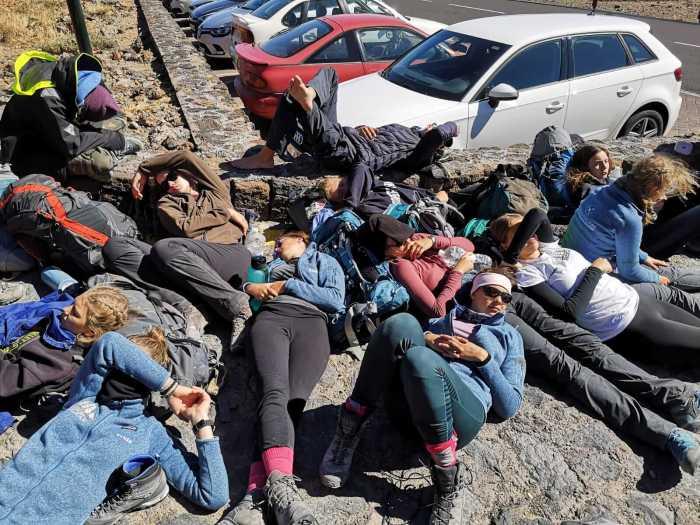 Teilnehmer liegen auf Felsen und ruhen sich nach der Besteigung des Teide aus.