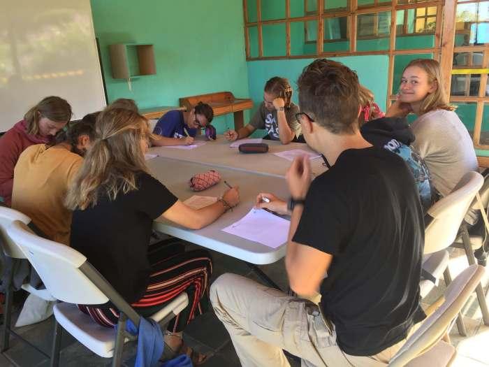 Kinder sitzen in der Sprachschule um einen Tisch und schreiben einen Test
