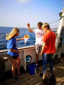 Schüler mit Wasserprobe auf dem Segelschiff