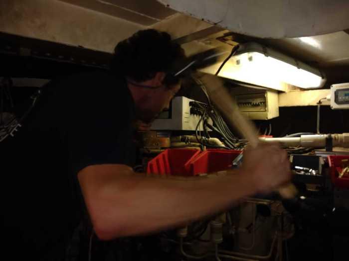 John geht mit Hammer auf die Maschine los