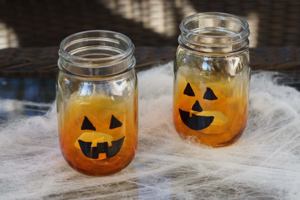 Decorate the jack-o-lantern candle holders with spider webs