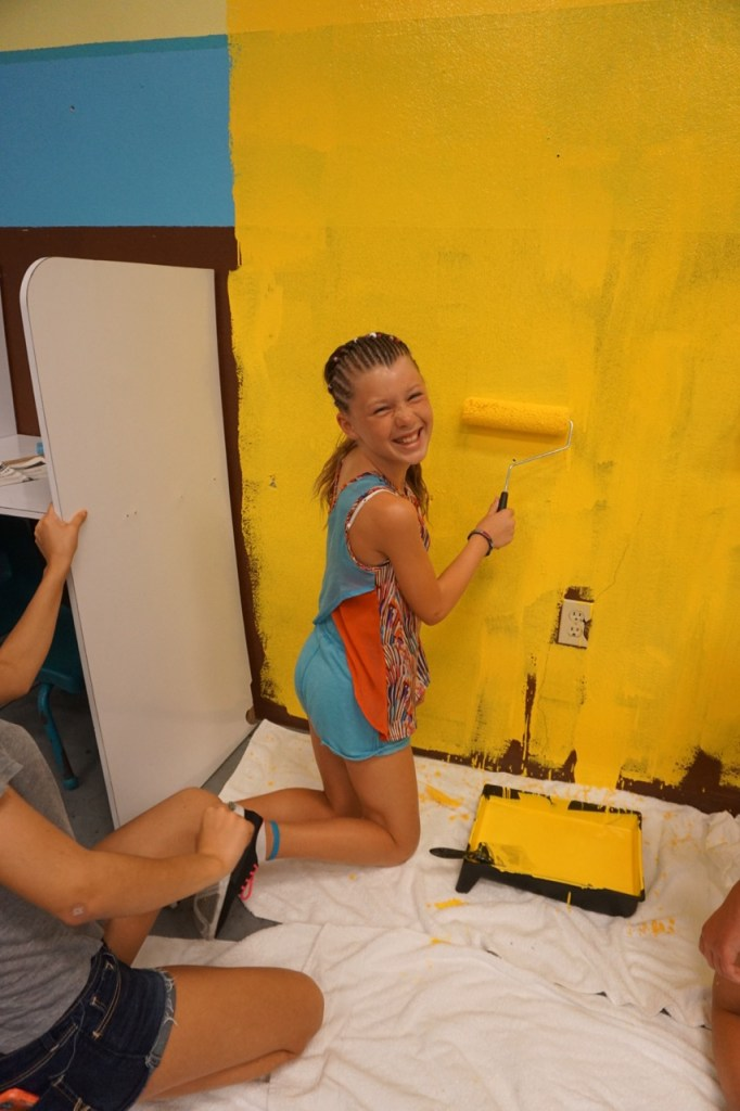 Little girl painting a classroom in the Turks and Caicos Beaches Teens volunteer completion certificates #BeachesMoms