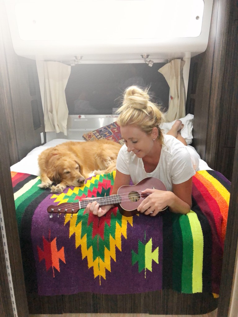 Playing a Ukulele inside of an airstream at Caravan Outpost in Ojai