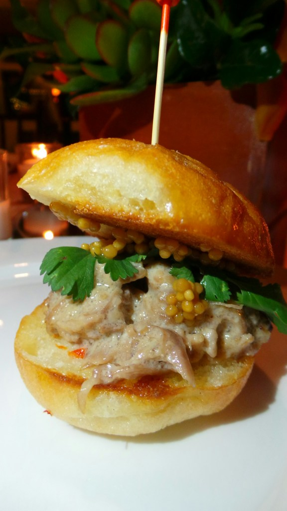 Coconut milk-braised pork slider with pickled mustard seeds and rooster sauce