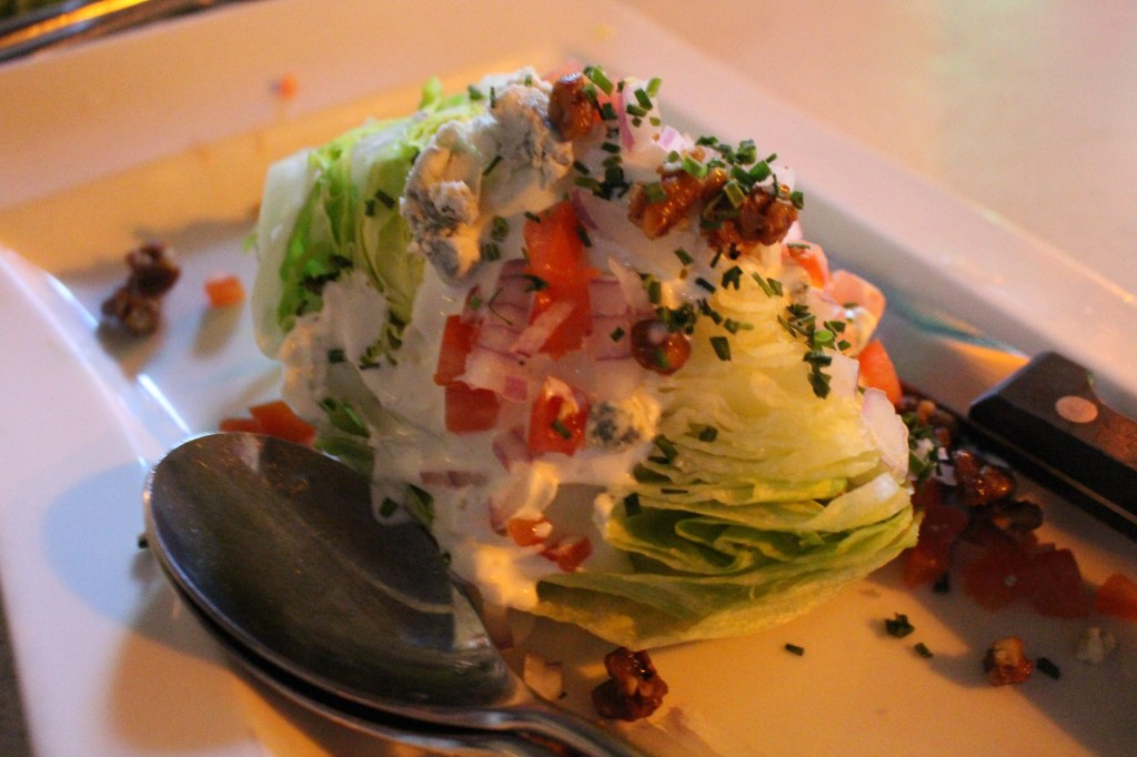 A wedge of Iceberg with crumbled bacon, bleu cheese, diced tomato, red onion, candied walnuts and bleu cheese dressing.