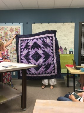 Trudy shows off a quilt made in a class