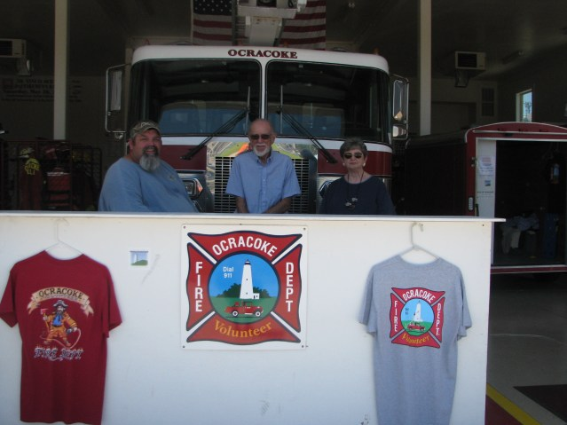 In addition to the annual Firemen's Ball, T-shirt sales provide income for the Ocracoke Volunteer Fire Department. Helping out are longtime volunteers Albert O'Neal, fire chief, Dick Jacoby, president of the OFPA, and Janey Jacoby, treasurer of the OFPA. Photo by P. Vankevich