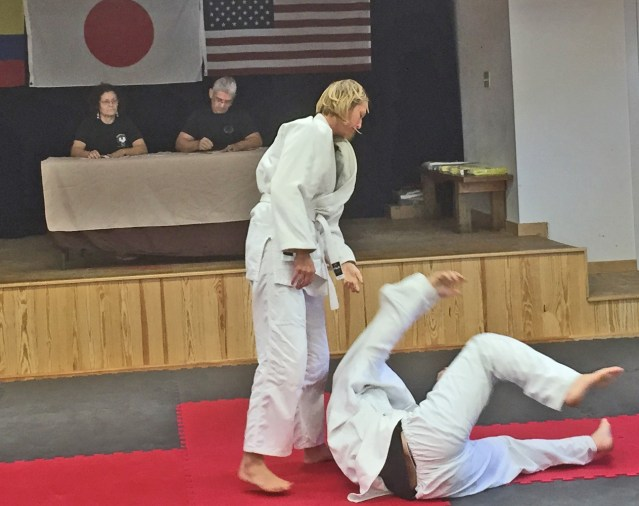Judo Jetta Brown flips Casey Robertson during the judo demonstration and ceremony. Patricia Lopez and Gustavo Sanchez judge from the stage. Photo by C. Leinbach