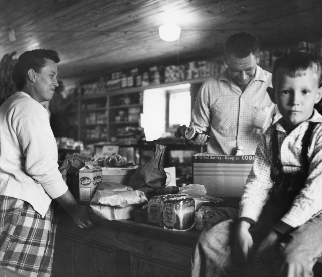 "Iona Teeter, and her son Carl ""Toad"" Teeter purchase sundries from Monkford Garrish at The Community Store, 1955. Photo from the Standard Oil Collection by Martha McMillan Roberts, courtesy of Ekstrom Library."