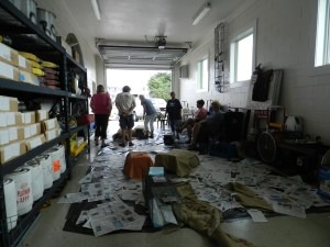 The Ocracats clinic in the Ocracoke Volunteer Fire Department. Trapped cats are in covered cages. Volunteers at rear organize the cats for surgery.