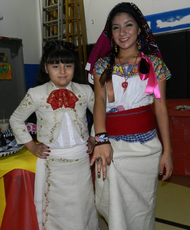 Ocracoke School first-grader Stephanie Flores Esparsa, left, and ninth grader Vanessa Lora model traditional clothing from Mexico. Lora later was crowned queen of the festival for selling the most 50-50 tickets.
