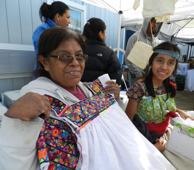 Laja Candelaria, left, shows her handiwork: hand-beaded decoration for a shirt in the style of the Puebla region of Mexico.