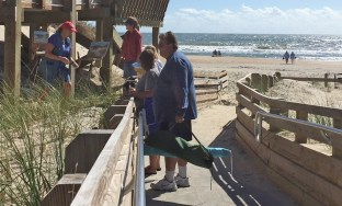 While painting the dunes at the Lifeguard Beach, Gail Smith and Joanne Geisel chat with curious beach-goers. Photo: Connie Leinbach