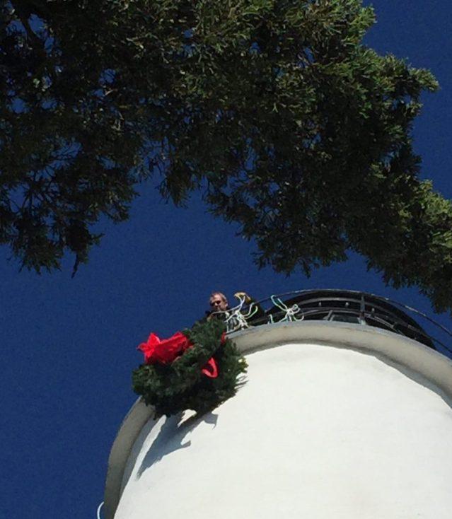 John Simpson hoists Christmas wreaths to the top of the Ocracoke NC lighthouse.