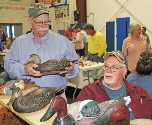 David O'Neal, left, featured carver at the first Ocracoke Waterfowl Festival April 21, talks with Scotty Robinson.