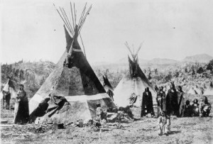 several Shoshone Indian people stand near two tipis