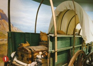 interior of covered wagon with trunk, food, and clothing