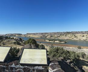 outdoor exhibits on a stone wall overlook a panoramic view of Snake River