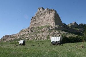 two covered wagons in front of large rock formation