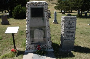 stone marker with plaque and gravemarker next to Oregon Trail marker set in a cemetery
