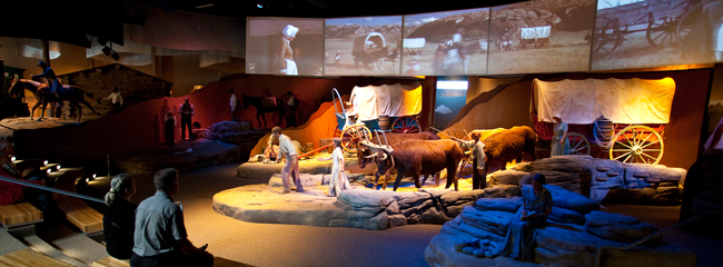 interior view of Oregon Trail exhibits with oxen and a covered wagon