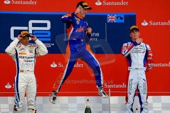 World © Octane Photographic Ltd./Chris Enion. GP2 British GP, Silverstone, Sunday 30th June 2013. Race 2 winner Jon Lancaster - Hilmer Motorsport celebrates on the podium with James Calado and Rio Haryanto. Digital Ref : 0732ce1d9562