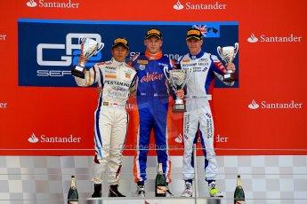 World © Octane Photographic Ltd./Chris Enion. GP2 British GP, Silverstone, Sunday 30th June 2013. Race 2 winner Jon Lancaster - Hilmer Motorsport celebrates on the podium with James Calado and Rio Haryanto. Digital Ref : 0732ce1d9584