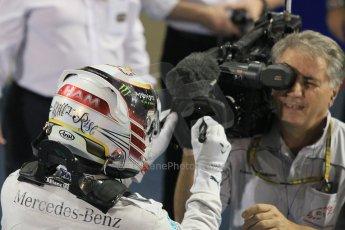 World © Octane Photographic Ltd. Sunday 23rd November 2014. Abu Dhabi Grand Prix - Yas Marina Circuit - Formula 1 Podium. Mercedes AMG Petronas – Lewis Hamilton - Race winner and 2014 World Champion signing the TV camera lens. Digital Ref: 1173CB1D0625