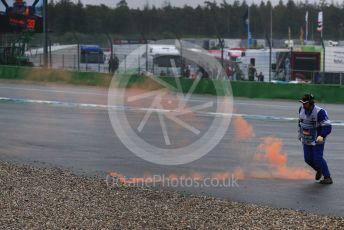World © Octane Photographic Ltd. Formula 1 – German GP - Race. A marshal kicks an orange smoke marker clear that was thrown on track from a Max Verstappen fam. Hockenheimring, Hockenheim, Germany. Sunday 28th July 2019.