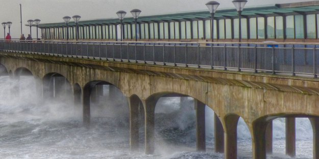 Concrete bridge over stormy seas.