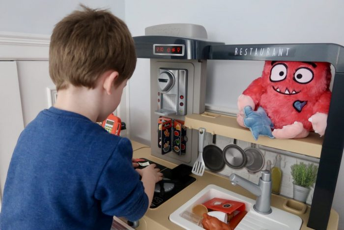 A little boy looking at a Smoby Chef's Kitchen toy with a Love Monster stuffed toy on the shelf