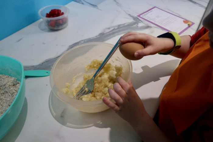 A child cracking an egg into a bowl of mashed banana