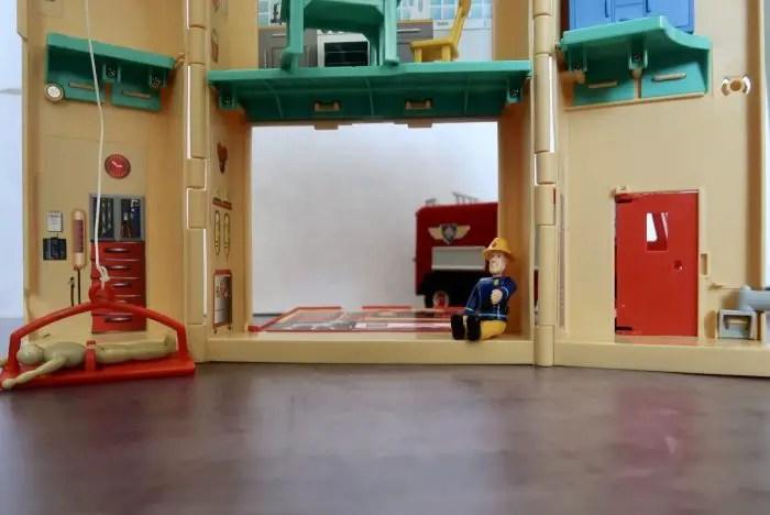 Fireman Sam sitting next to an open door