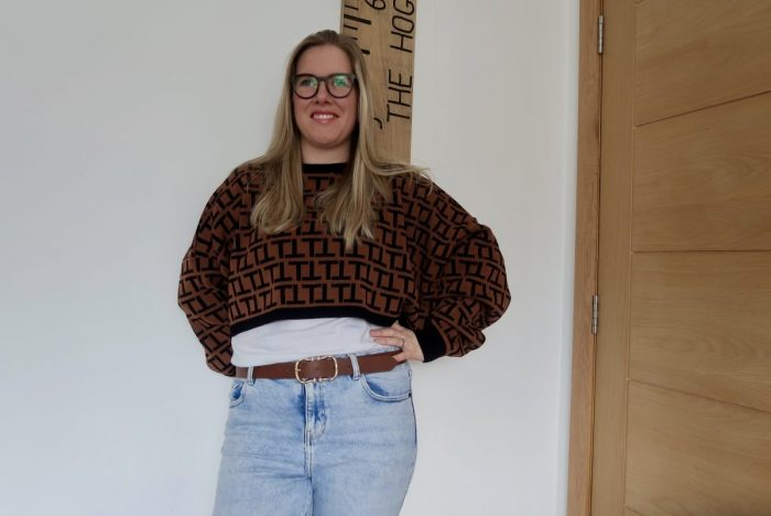 A woman wearing a brown and black patterned cropped jumper and pale jeans. She is standing with her hands on her hips.