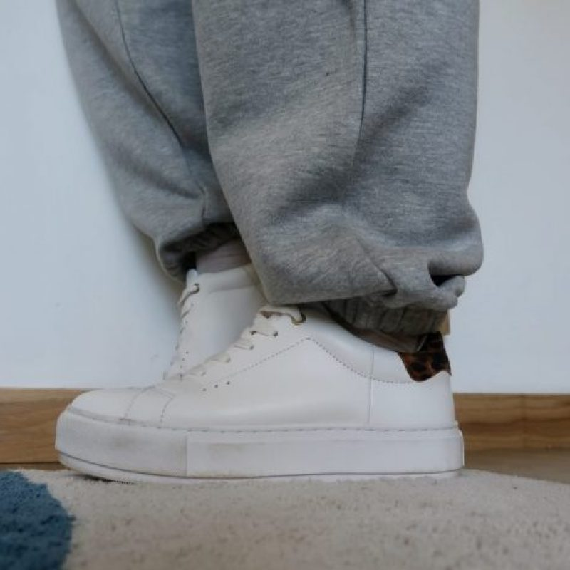 some white trainers with a leopard print trim, worn by someone wearing grey joggers