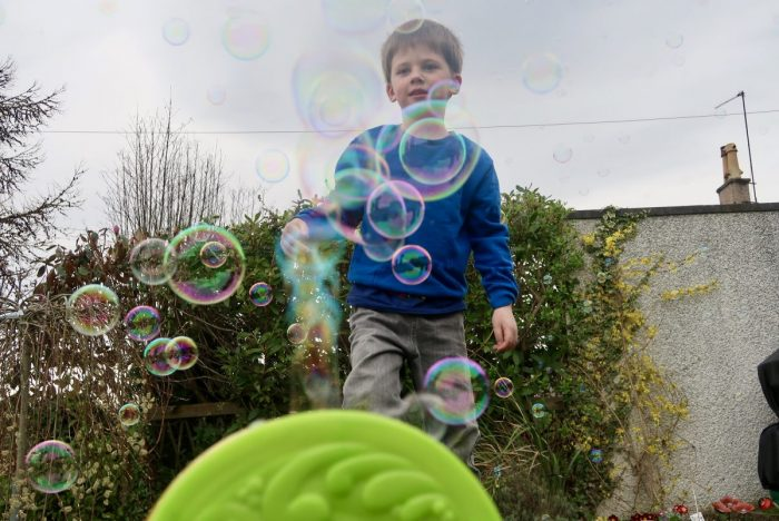 A bubble machine with bubbles coming out of the top