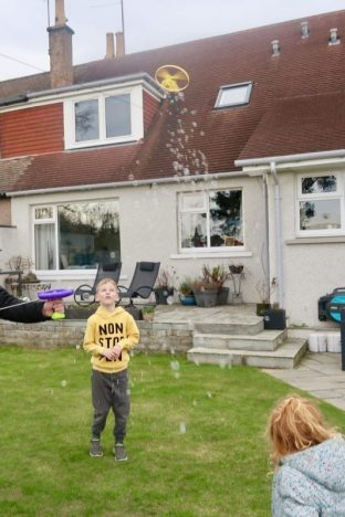 Children standing in a back garden watching a helicopter bubble toy in the sky
