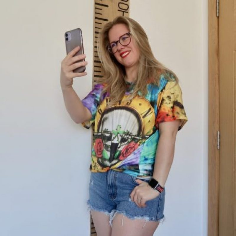 A girl wearing denim shorts and a tie-dye t-shirt holding out her phone and taking a selfie