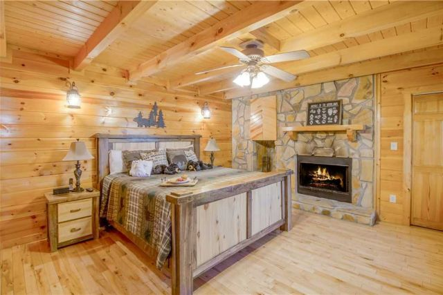 A room for all seasons - In winter the fireplace of the main floor's master suite will cast a warm, romantic glow over the wood-planked walls and beamed ceiling; in summer the ceiling fan will lull you to sleep with its gentle breeze.
