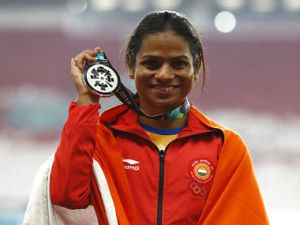 India's Dutee Chand celebrates on the podium after winning the silver medal in the women's 100m final during the athletics competition at the 18th Asian Games in Jakarta, Indonesia, Sunday, Aug. 26, 2018. (AP Photo/Bernat Armangue)