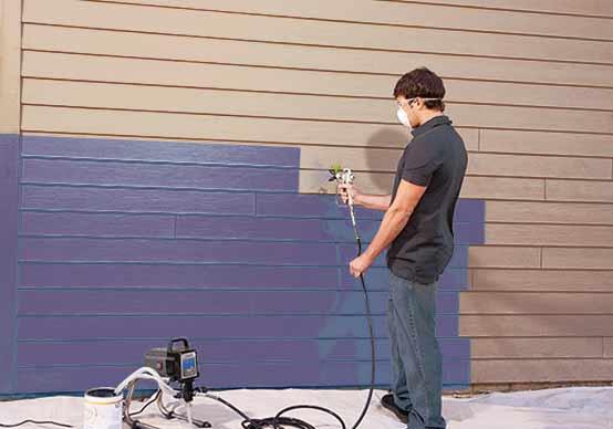 мужчина красит стену из сайдинга распылителем