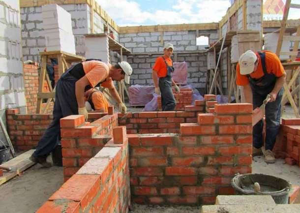 бригада строителей выполняет кладку кирпичной стены