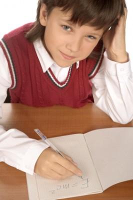 Chlapec, který píše rukou do sešitu