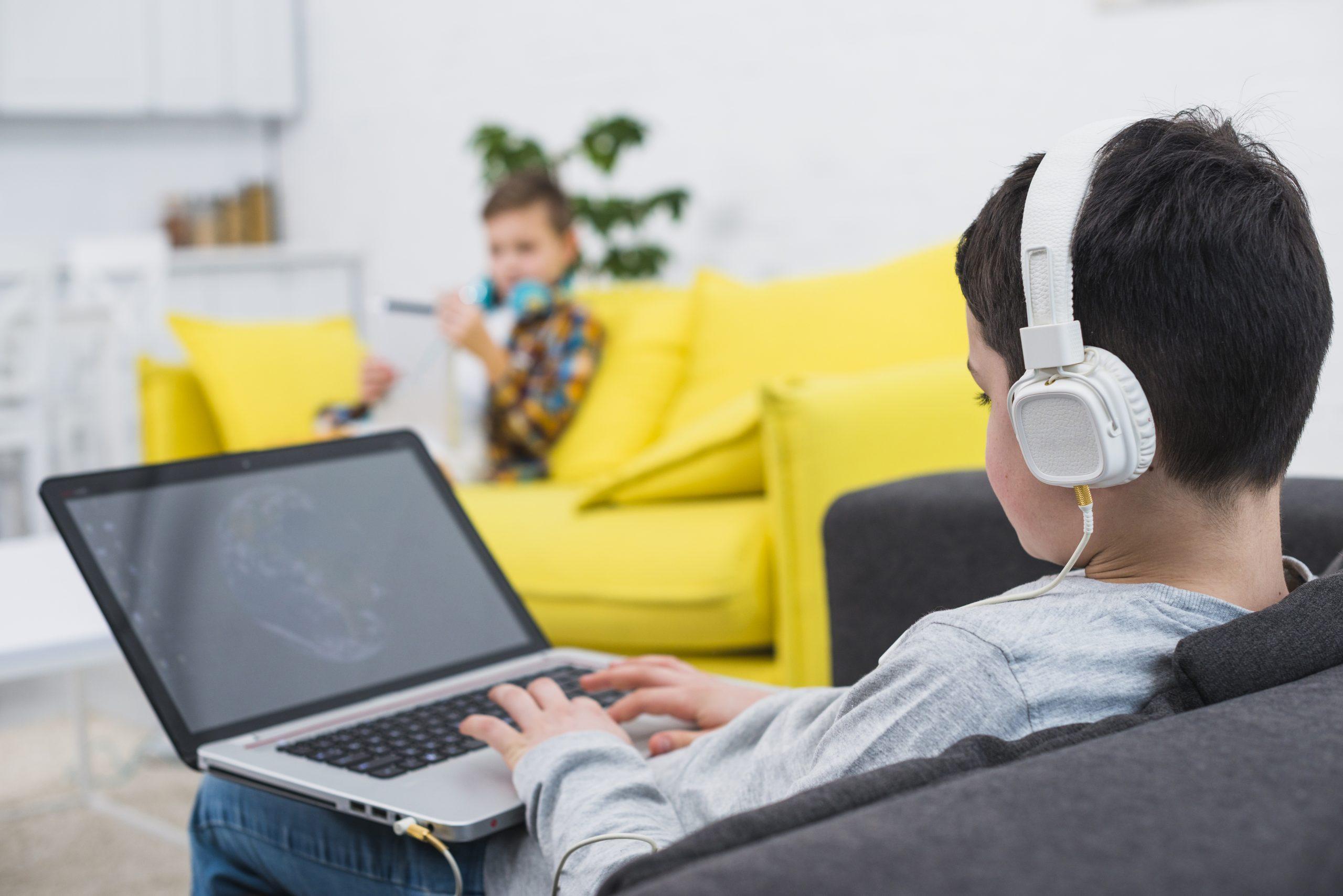 Chłopiec w słuchawkach gra na laptopie