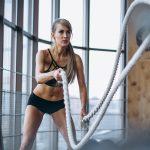 Kobieta trenująca crossfit ćwiczy z liną na sali gimnastycznej