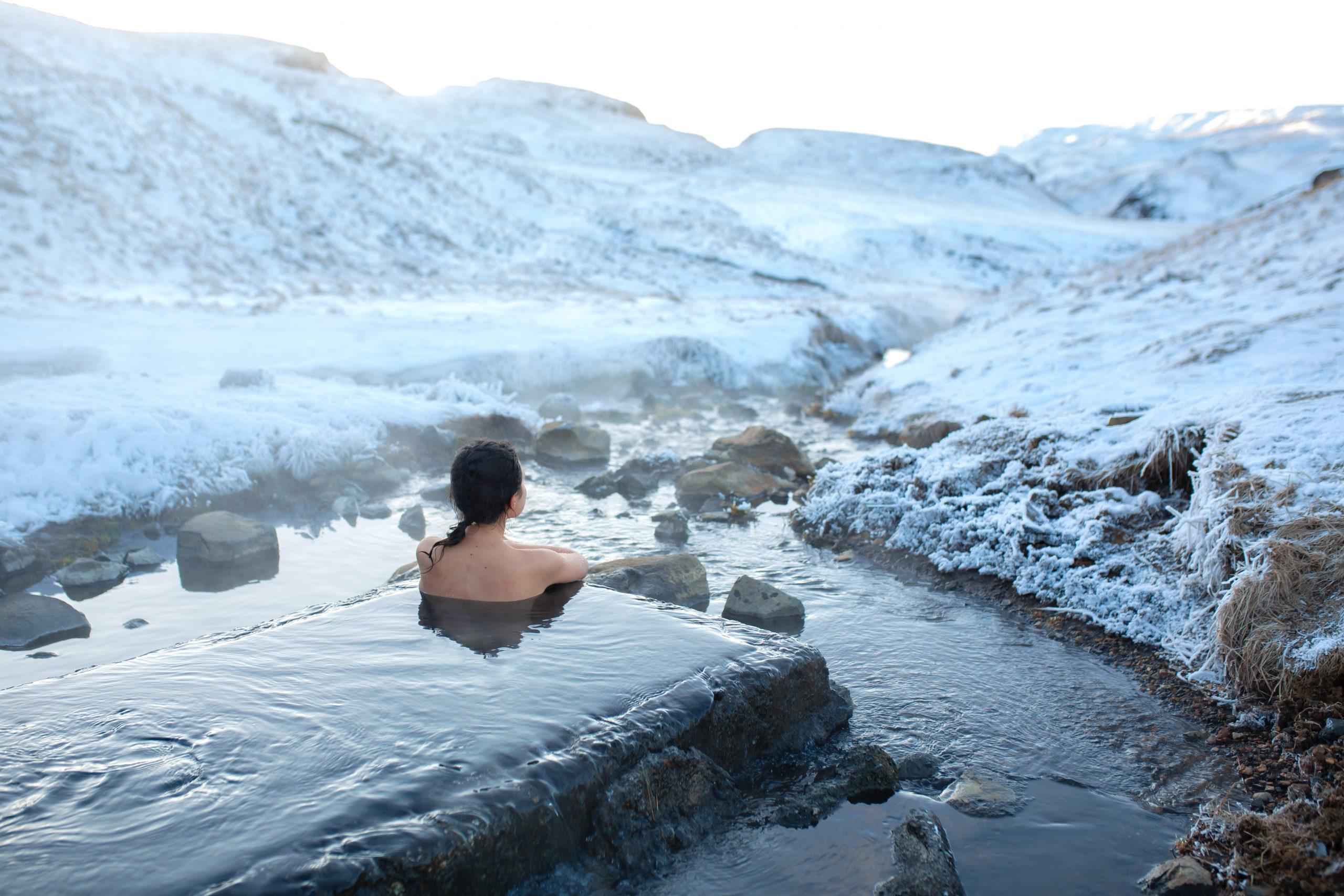 Kobieta kąpie się w przeręblu w otoczeniu śniegu