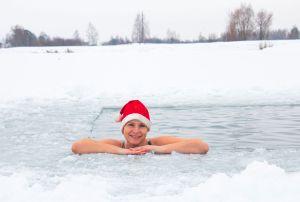 Morsowanie. Jakie to uczucie? Jak długo można być w wodzie? Jak wchodzić do wody? Jak się ogrzać po wyjściu z wody? Uśmiechnięta kobieta morsuje w przeręblu ubrana w czapkę mikołaja.