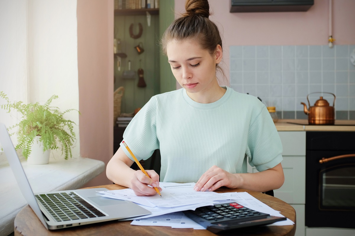 Teenage girl at kitchen table doing homework with computer, calculator and papers