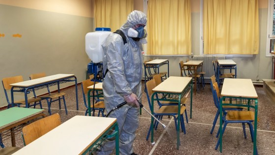 Man in protective suit sprays empty school classroom with disinfectant